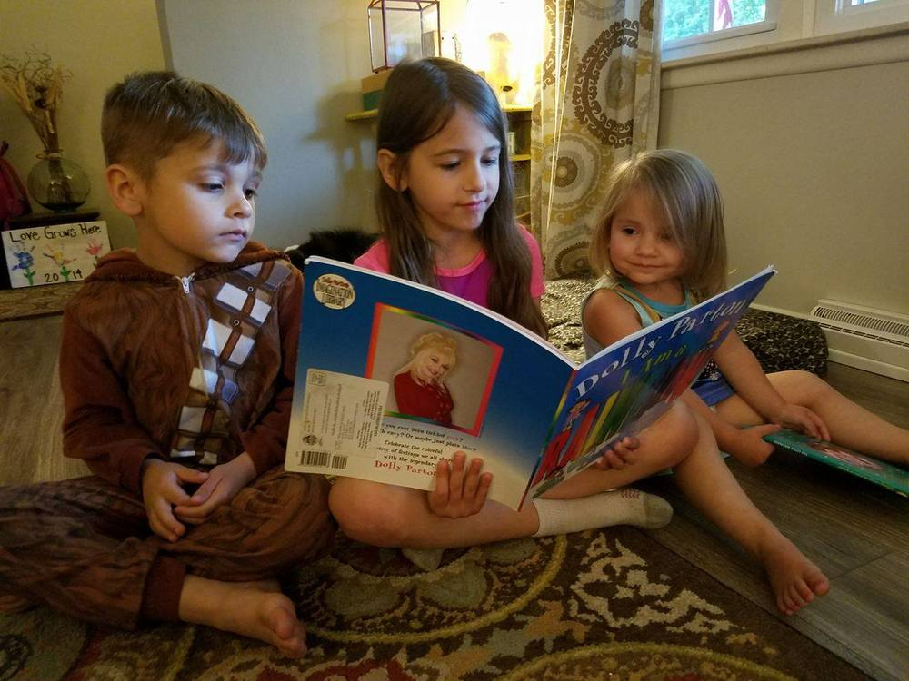 The children of Matt and Amanda Koch, of St. Joseph, read a Dolly Parton Imagination Library book (Left to Right: Abe (6), Emma (8), and Eva (2).