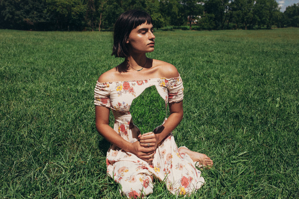 surreal portrait of a girl in a long dress in the grass