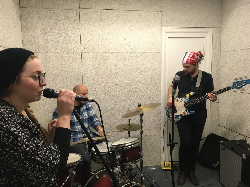 Gold From Grief singer Kelsey Hopkins, drummer Michael Ortiz and bassist Lynn Roose III cram into a packed practice space below Strongwater Food and Spirits. (Photo by Zachary Kolesar)