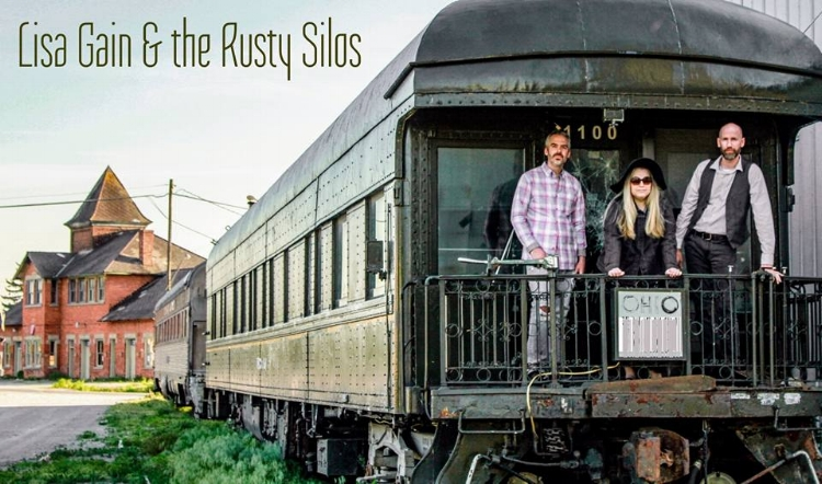 "Lisa Gain & the Rusty Silos pose on a train that is marked with ""Ohio."" The members of Lisa Gain & the Rusty Silos —Lisa Gain, James Boza and Bryan Rupejko—have individually been in the Ohio music circuit for 20-plus years. (Photo by  JLM Photography)"