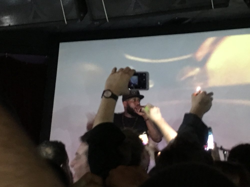 Brooklyn rapper Talib Kweli urges everyone at Ace of Cups to put their cell phones and lighters in the air to brighten up the venue. Kweli had the crowd moving throughout his entire 90-minute set at Ace of Cups on Feb. 15. (Photo by Zachary Kolesar)
