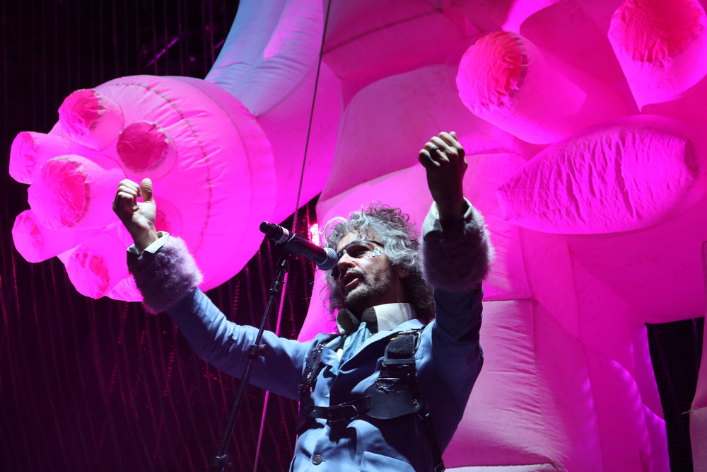 "Wayne Coyne of The Flaming Lips strikes a pose in front of a giant pink robot during the band's performance of ""Yoshimi Battles The Pink Robots Part 1."" Coyne and company brought out many tricks for Saturday's closing set. (Photo by: Ana Goffe)"