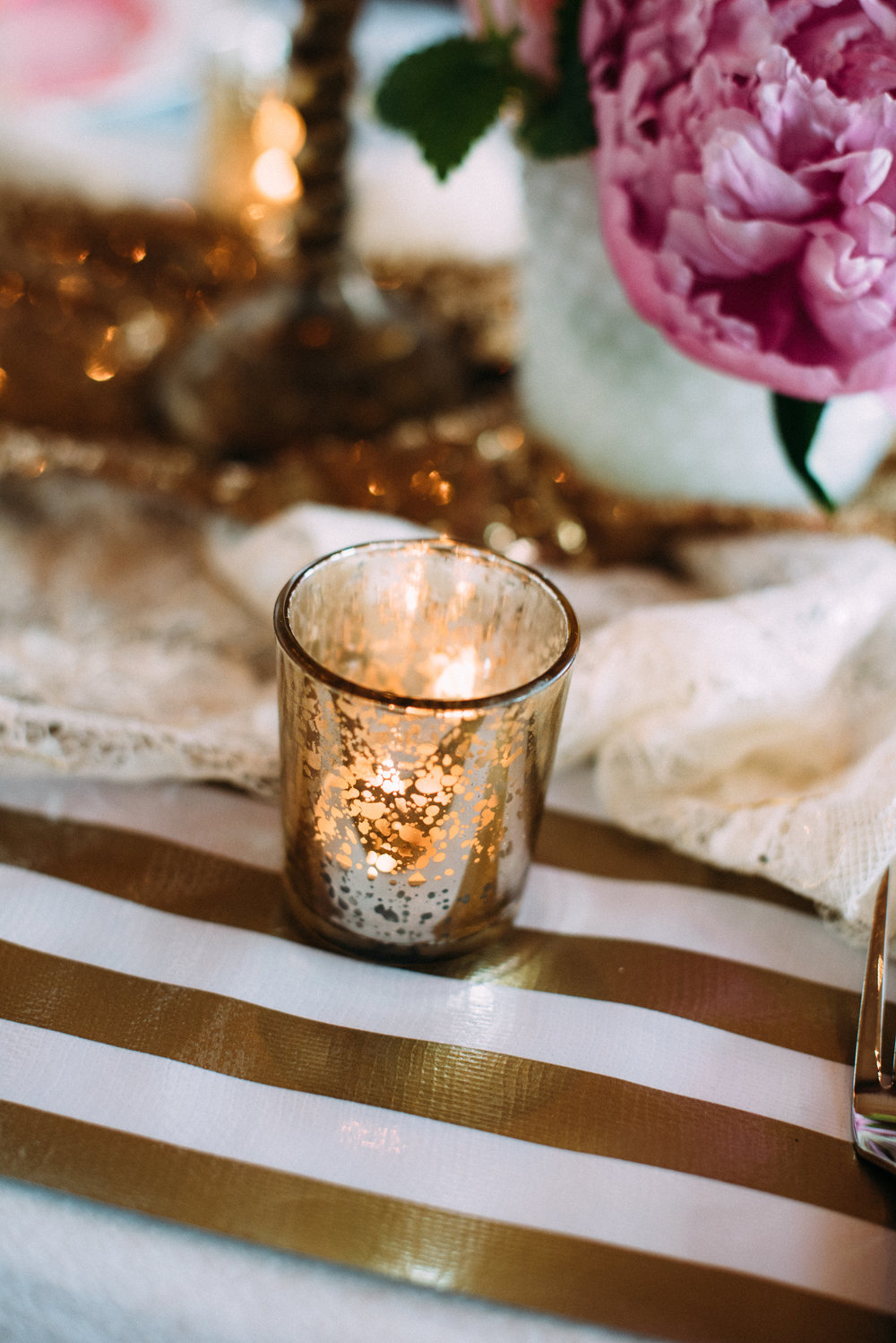 Create loose groupings of threes down the table, pairing flowers, candles and decor together.