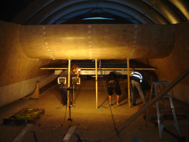 Raising the bridgedeck panel into place for bonding and glassing with Acro Props.  We completed the main assembly in 10 days.  It was one of the most rewarding times of the build as the boat goes from a pile of parts to a defined structure you can move within.  May 2010.