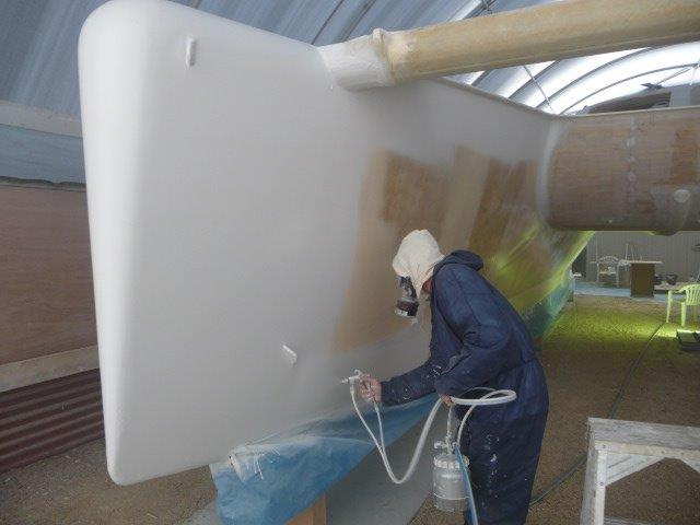 "The first ""shoot"".  Russel putting the stbd hull into ""sprayable"".  In 5 weeks Russel and Michael got both hulls sealed, bogged, faired, spray faired and sprayed again with High Build Primer.  May 2013."