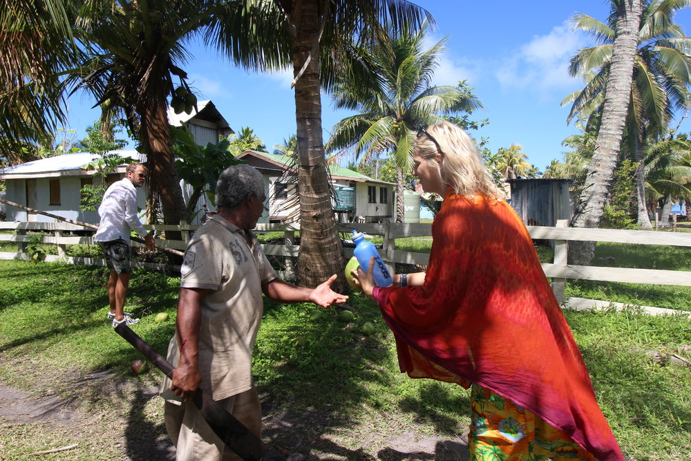 Holly receiving a fresh coconut to drink from TAI. With coconut palms growing throughout the Village, they are used for all sorts of things not just the delicious water, milk, and flesh but the fibers are used for making rope and the fronds for weaving.