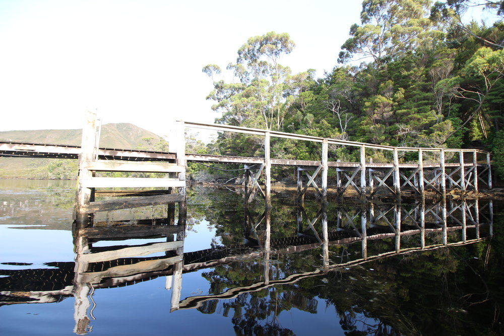 The jetty to Claytons house in Port Davey. The tannin stained waters on a calm day create a mirror reflection of the picturesque surrounds.
