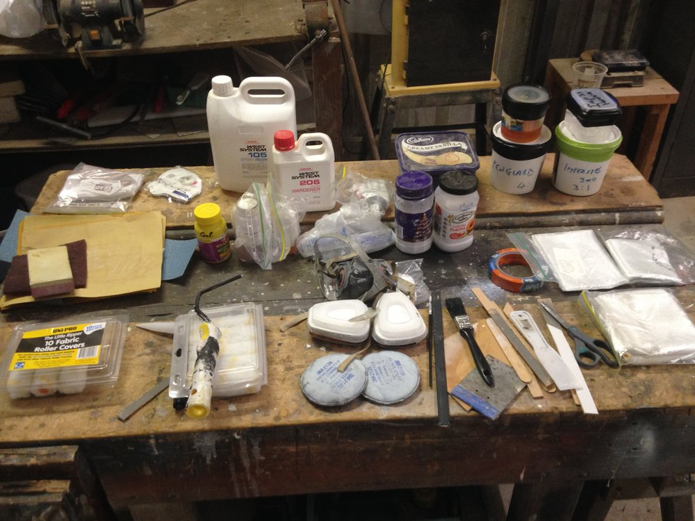 This is my fiberglass repair kit including paints.  It has a small quantity of everything Roam is built from.  Its all laid out here on one of the benches in John's shed.  After 18 months onboard we had used a few things (mostly for fixing other peoples surfboards) and some things had gone off and needed replacing.   I am also not carrying the quantities resins that I was before.  The hardners go off in the heat and expire so I carry now enough for small jobs and if we ever needed to do a bigger repair we would just have to stock up for the job.