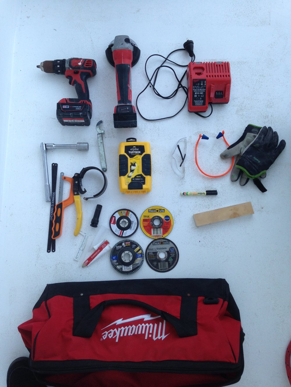 "This is the ""Milwaukee"" tool bag.  Named for obvious reasons.  The gear in here is pretty self explanatory.  Of note is the 18V Grinder.  I was on a race boat doing a delivery a few years back and its carbon mast came down in spectacular fashion in the night.  It had rod standing rigging that needed cutting so we could abandon the rig before it punched a hole in the deck and hullside.  The guys onboard were well prepared and had a battery grinder to cut shrouds but I remember watching the bloke who made the cut trying to operate the grinder, shield his eyes with one hand as the sparks flew.  For the 2nd cut that night some sunnies were used.  I now always make sure that the cutting disc is in the grinder for passages and there is some safety glasses right next to it.  You are going to be pretty upset the day you have to lose your rig, no point going blind over it too though.  If you think you are going to be effective in a worst case situation with a hacksaw you are dreaming."