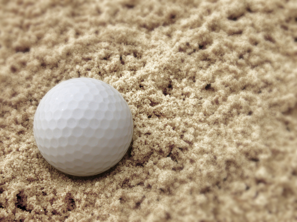 Golfball im Sand