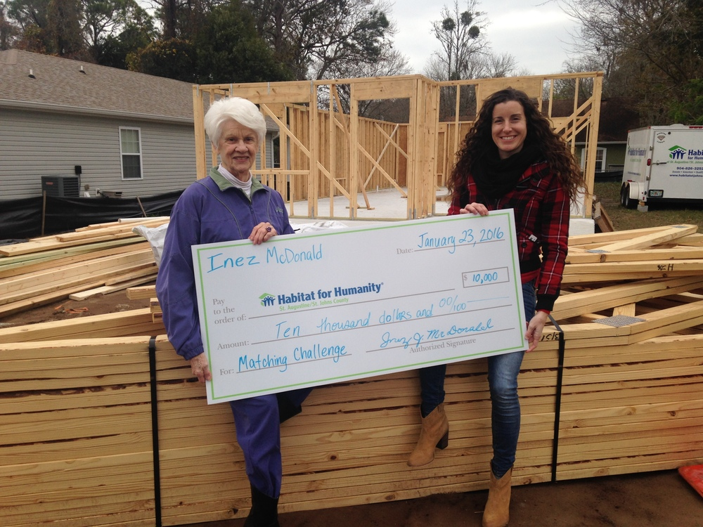 Local patron Inez McDonald presenting her donation to Habitat Executive Director Alia Reimer