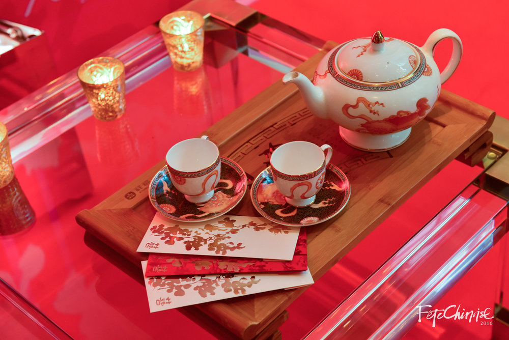 A modern take on the traditional tea ceremony, this vignette features the custom china at Shangri-La Hotel on a wooden tea tray, with beautiful lucky money pockets by PALETTERA.