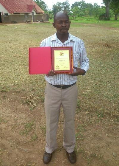 Opolot Kokas proudly displaying his facility's award