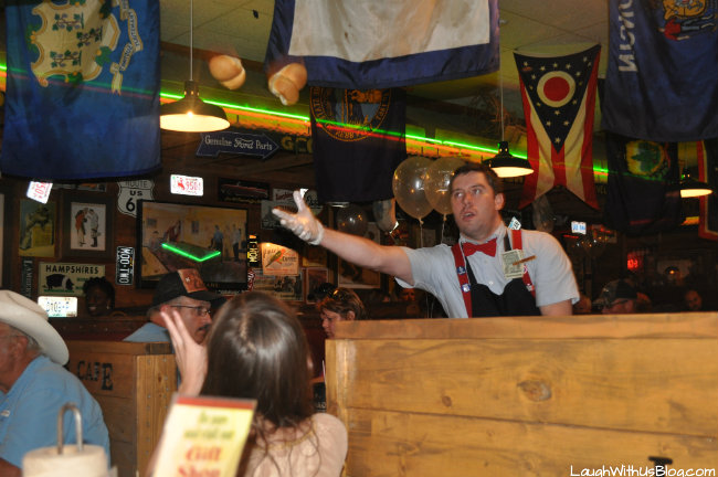 Lamberts employee tosses a pair of warm rolls to a waiting customer.