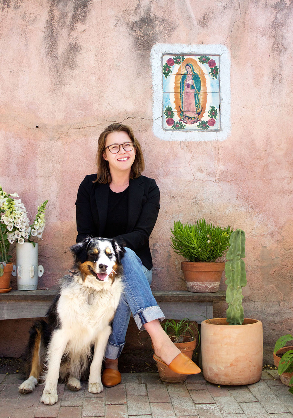 Amanda and Otis, her Australian Shepard, relax outside by a tile portrait of the Virgin Mary installed by her grandfather, who lived in the adobe before her.