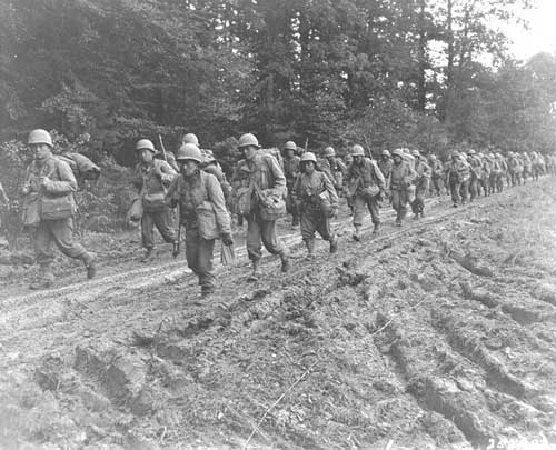 The 442nd Regimental Combat Team_ hiking up a muddy French road in the Chambois Sector_ France_ in late 1944.