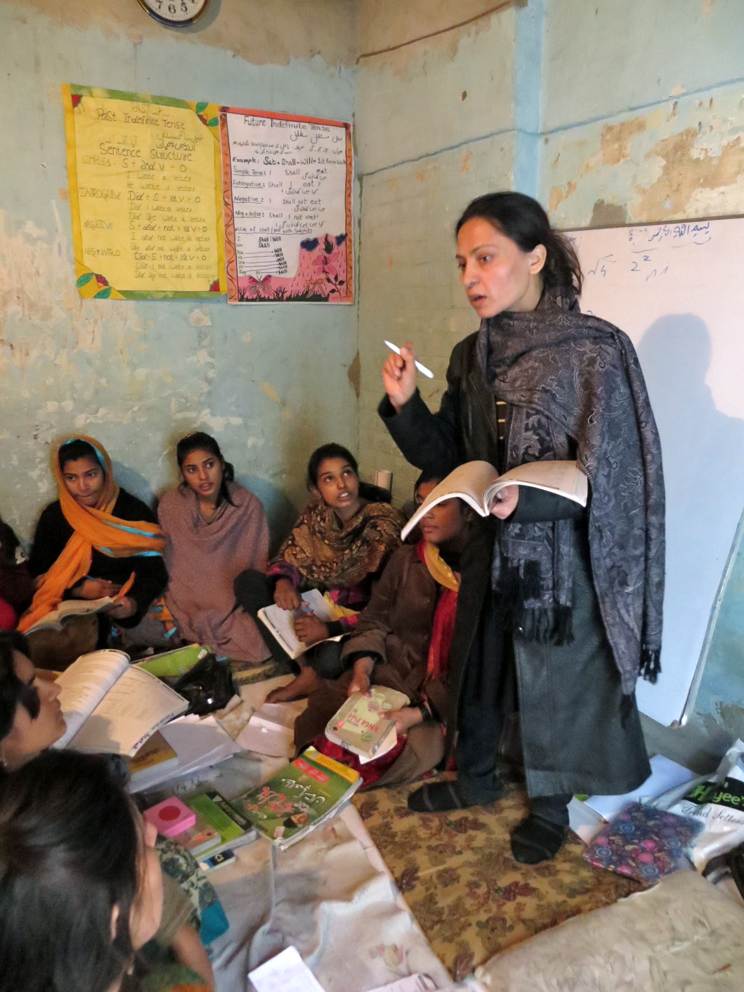Nilofer Bano Armanshah, reviews a lesson on homonyms to help her students prepare for the 9th and 10th grade board exams. She teaches at a two-room school run by the NGO Plan International, which offers women who dropped out of school a chance to complete their studies.