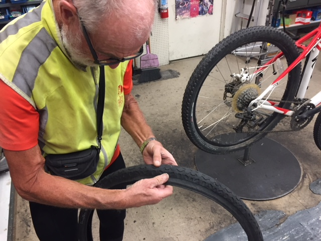 Francois inspects the tire that was damaged on his bicycle.  His tire and wheel were fixed at Kevin's Bikes in Merced and he was on his way after a couple of hours.  Photo: Steve Newvine.