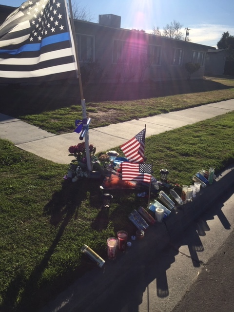 A display of flowers, candles, an American flag, and a cross in front of a residence in Newman. Photo- Steve Newvine
