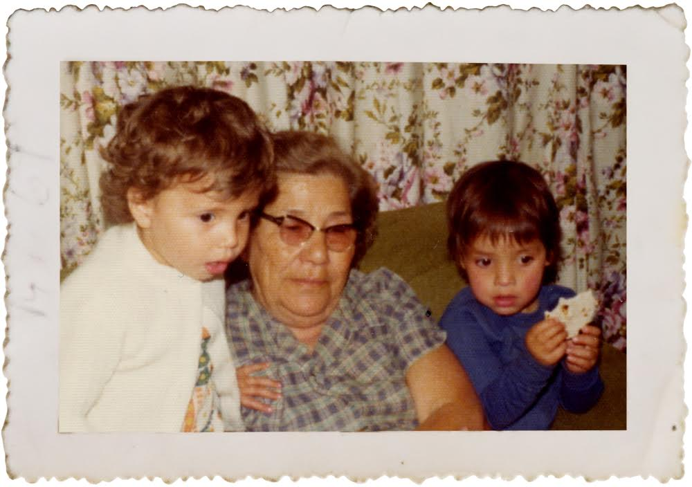Yvette Marquez-Sharpnack (R) with her grandmother, Jesusita, holding a homemade flour tortilla and cousin Brenda (L) in 1975. (Photo Courtesy: MuyBuenoCookbook.com)