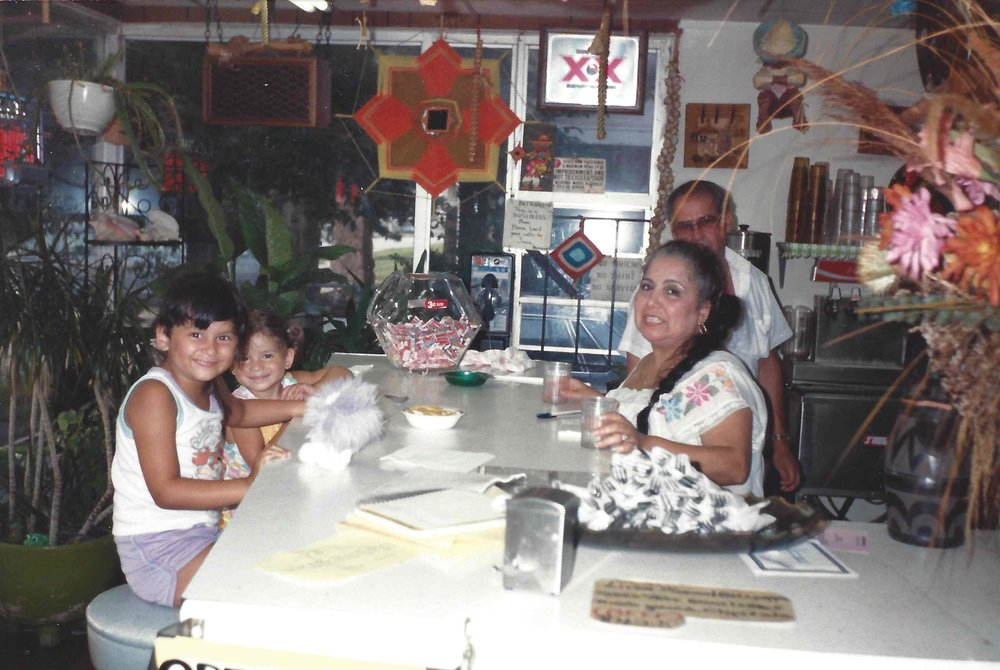 Gina (l) smiles while sitting at the booth with her sister Angelique (r) at their grandparents' restaurant Lupe and Bea's Texican restaurant in Memphis, Tennessee. Their grandmother Beatrice (l)  and her friend Esteban Nodal Morales (r), a close friend who also helped at the restaurant, stand behind the booth.  (Photo Courtesy: Angelique Sloan)