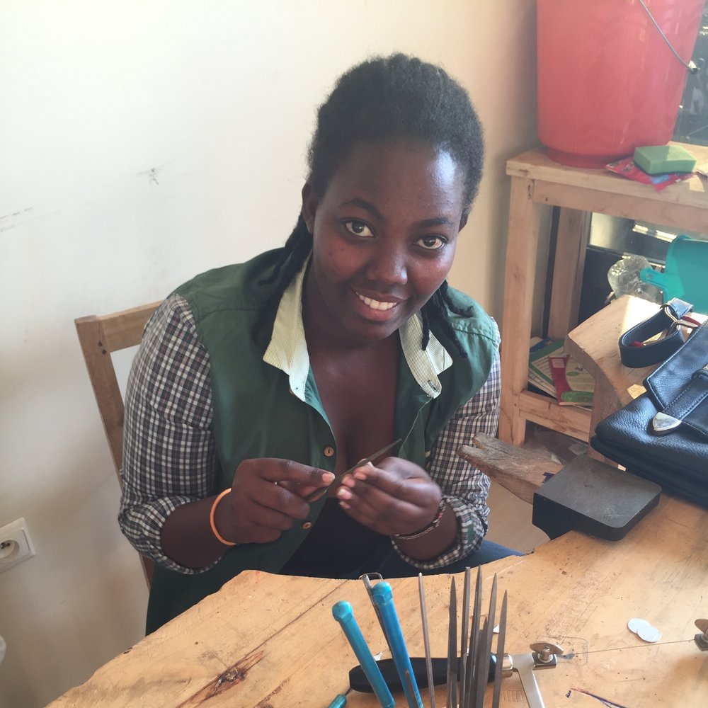 """Flora Murekatete Flora Murekatete is a 23 years old metal smith who graduated from Secondary School in Nyamata. Flora's family was terribly impacted by the 1994 Rwandan Genocide and has struggled to overcome poverty and trauma since then. According to Flora, """"To be in Abari Collective is to plan my future and journey in my whole life. I know now I will have a wonderful future from the success of Abari Collective because it will provide me economic empowerment."""" As a metal smith, Flora plans to support her family, help her community and become a role model for other young girls in her village."""
