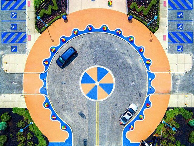 A lollipop style roundabout scratches the edge of a summer beach boardwalk.
