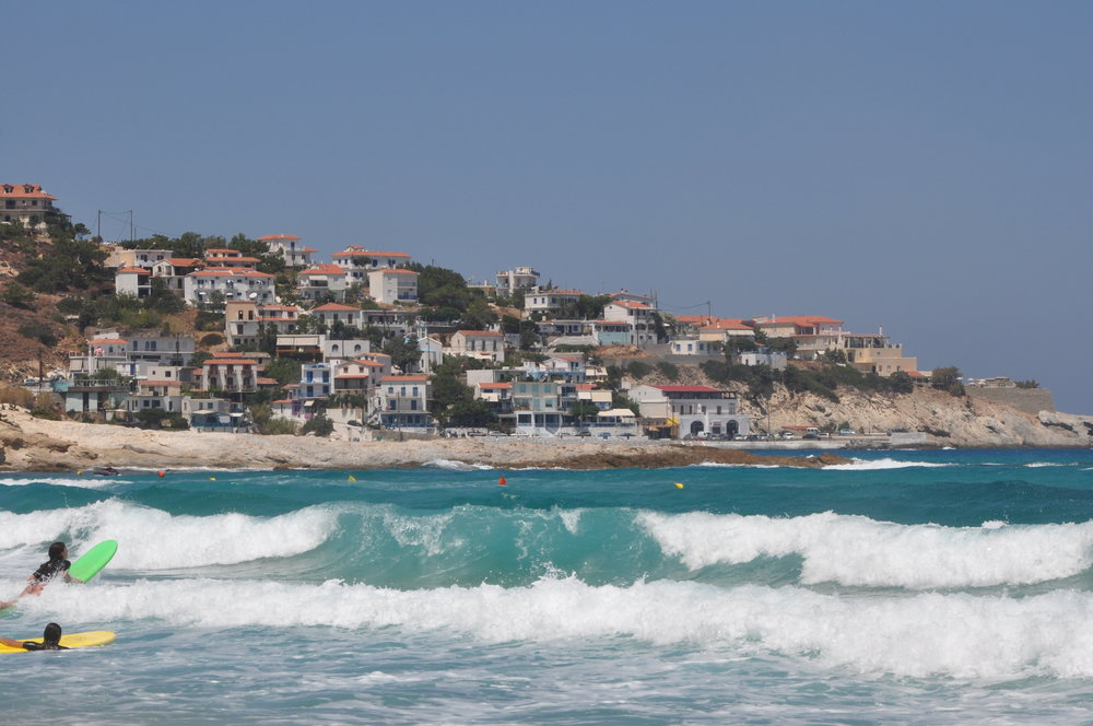 Surfers paddling out at Mesakti Beach, Ikaria, with a view of Armenistis village