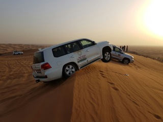 One Of The Desert Tour Vehicles Racing Over A Sand Dune