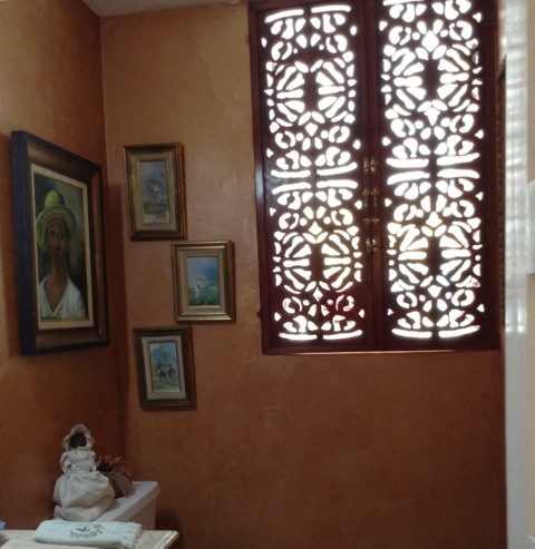 Delicate fretwork doubles as privacy shutters in the powder room of this historic Jamaican home.