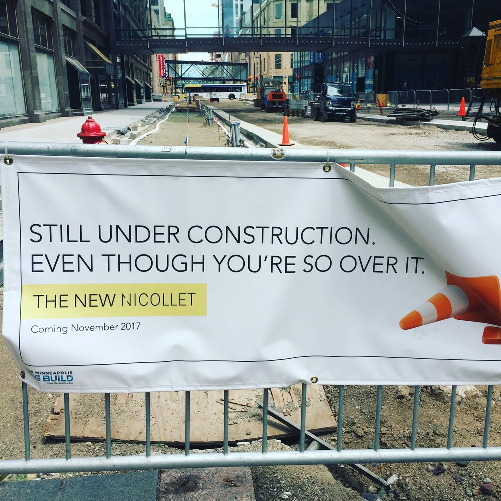 """[Photo of construction site with sign that reads """"still under construction even though you're so over it.""""]"""