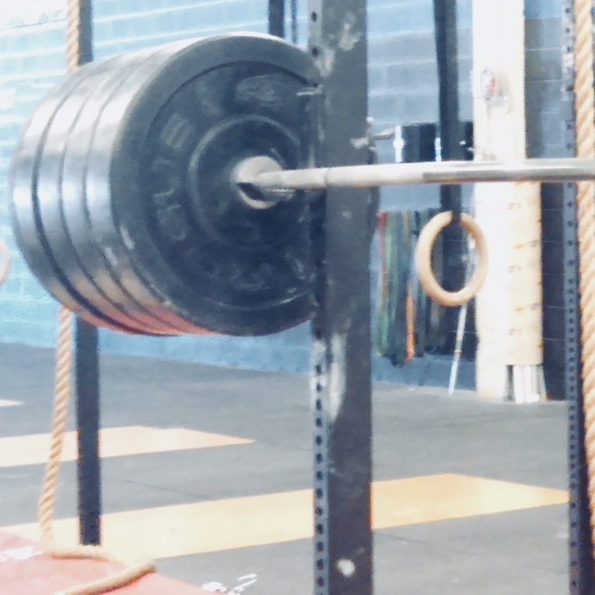 [Photo of a squat rack with stacks of plates on the bar]