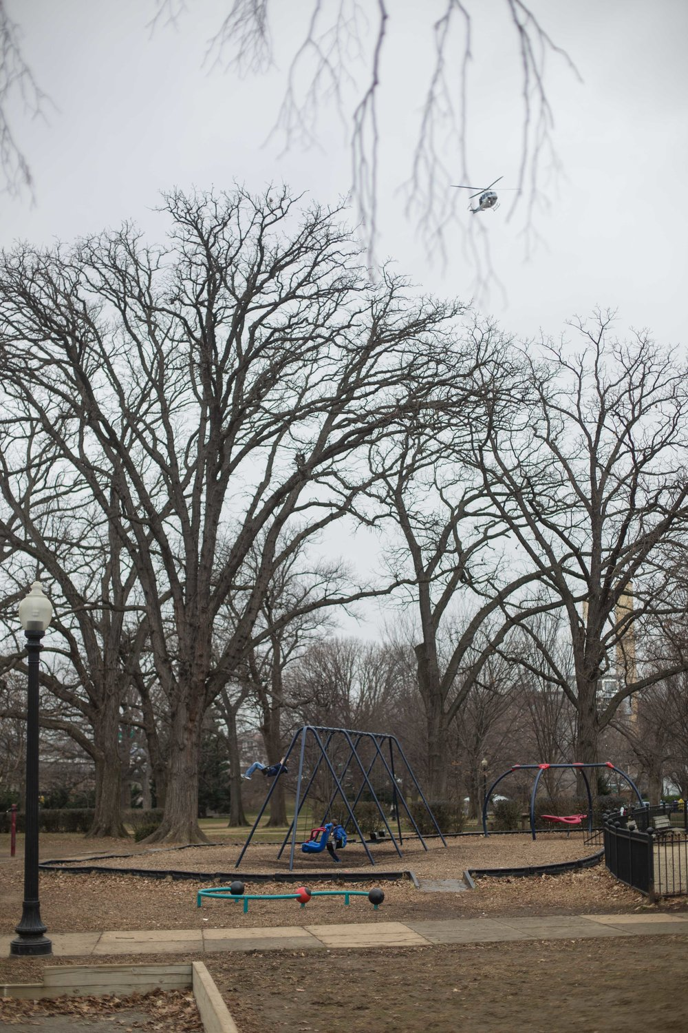 A child swings with his friend while a helicopter patrols overhead - January 20th, 2017