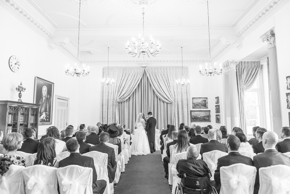 A wide-angle shot of the wedding ceremony helps to set the scene before moving in for close-up shots.