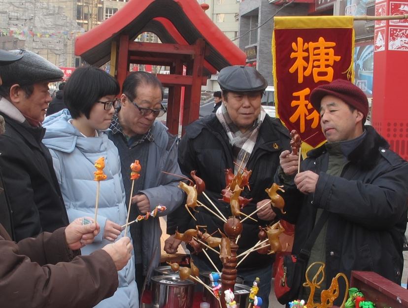 李占恒(右二)与他的作家老友们逛中国年货市场,对捏糖人儿的手艺叹为观止。