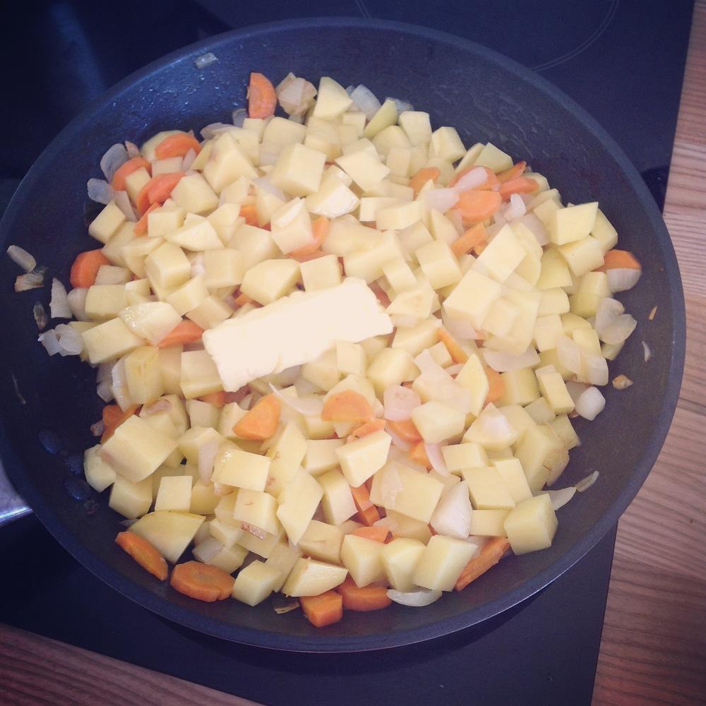 Apcepam sagriezto sīpolu sviestā uz nelielas uguns, lai tas nepaliek brūns, bet caurspīdīgs. Pievienojam kartupeļus un burkānus, nedaudz sāli. Apcepam 5 minūtes.