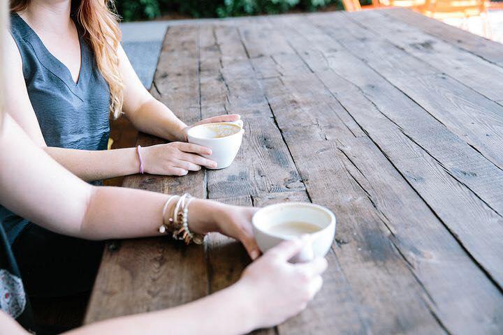 women talking holding coffee cups.jpg