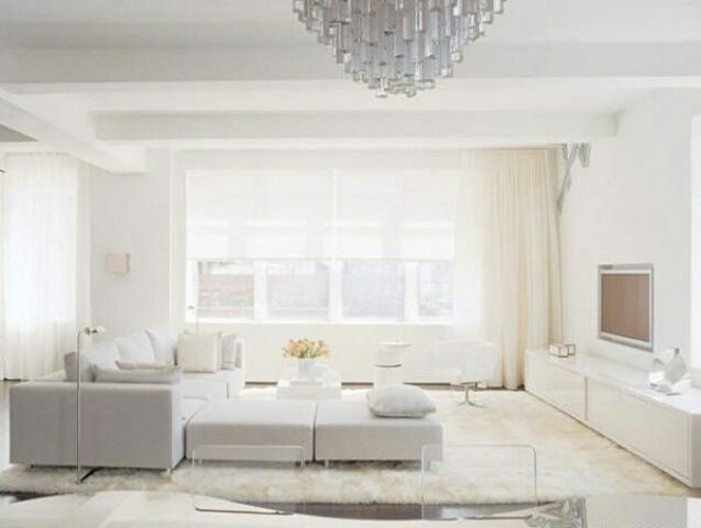 Living space with various shades of white, contemporary with elucite chairs in dining area.