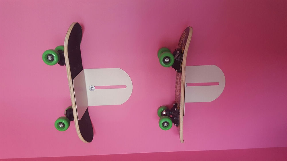 I upcycled these bookends and used them as a shelf to hold the skateboards.  The skateboards can be easily grabbed whenever the girls want to go outside for a ride.  Technically they can add items to the shelves, but they don't because they want to just grab their skateboards and go.  This was a fun way to add color to the room.