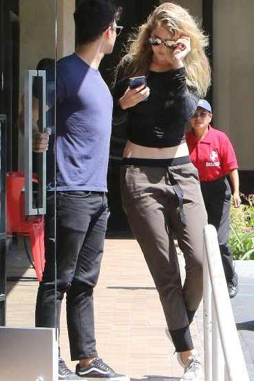 Gigi Hadid headed out with beau Joe Jonas wearing adidas Yeezy Boost 350 Sneakers, Line Dry Britt Pants, and Gypsy 05 Bamboo Shirred Long Sleeve Top.