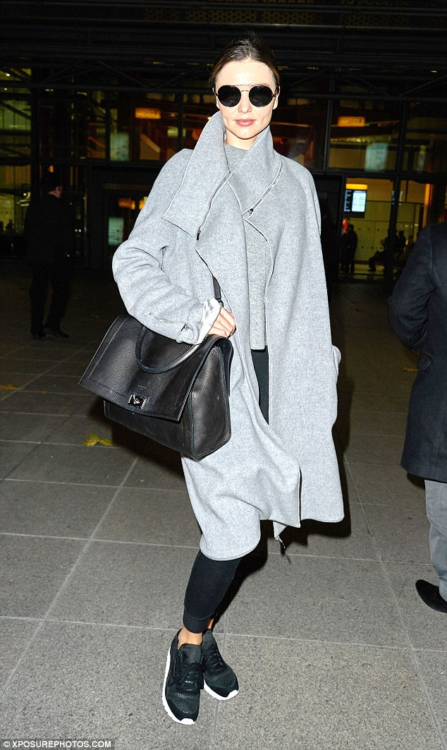 Miranda Kerr hit Heathrow Airport in London pairing an Amanda Wakeley Ito Grey Wool and Shearling Coat with a fresh pair of Reebok Classics.