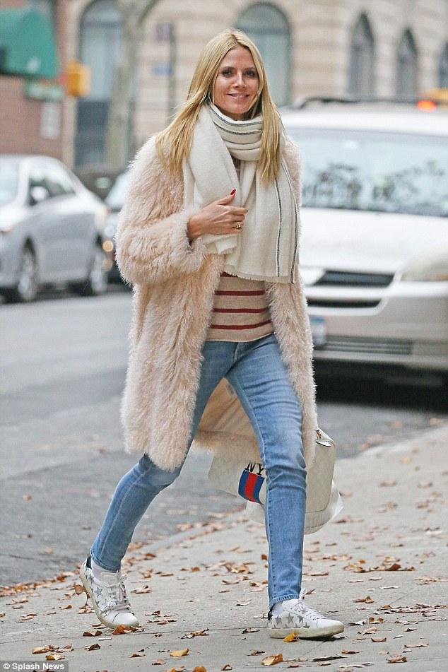 Heidi Klum shot a smile in NYC in Saint Laurent Star-Appliqued Leather Sneakers and a cozy Elizabeth and James Hart Coat in Nude.