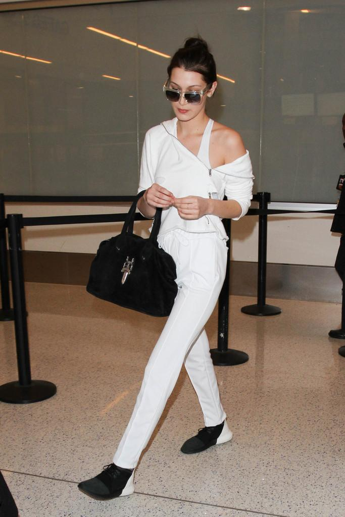 Bella Hadid high tailed it to LAX where we spotted her flashing a pair of adidas Originals Tubular Defiant two-tone sneaks with Brashy Tracksuit Pants. This. Is. Cute.