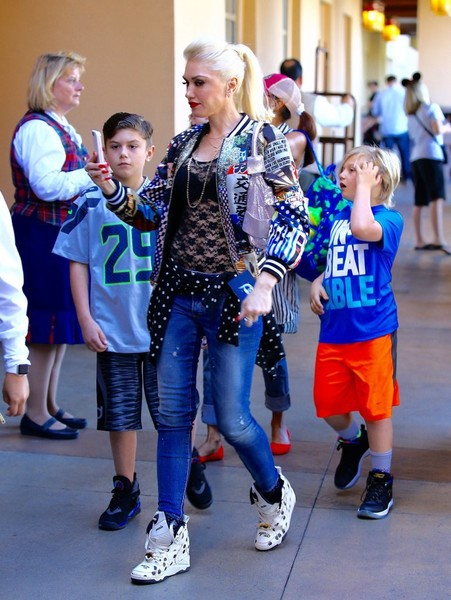Gwen Stefani was snapped on a weekend Disney outing with her tribe wearing a Play Comme des Garcons Merino Wool Cardigan Sweater in Polka Dot, Reebok x Melody Ehsani Polka-Dot Blacktop Pump Sneakers, Dsquared2 Medium Waist Twiggy Jeans and a Libertine Japanese Print Bomber Jacket.