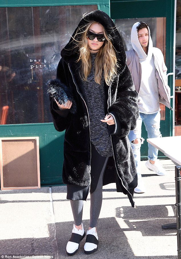 Gigi Hadid was spotted wearing a mink coat,yoga pants, and a pair of Low Top Elastic White sneakers by Filling Pieces.
