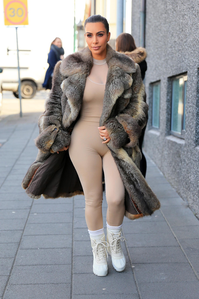 Kim Kardashian traipsed around Iceland (yea...hello!) in a head-turning outfit, pairing her nude bodysuit with a fur coat and white  Yeezy 950 boots.