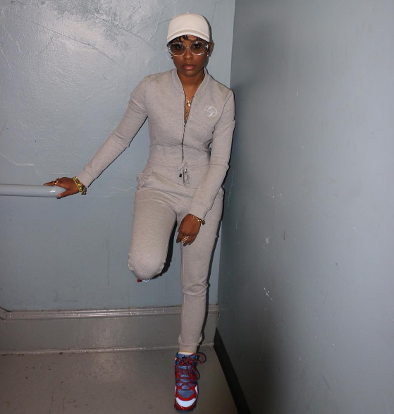 Back like she never left, DeJ Loaf posted up in a greyjumpsuit and in Marc Jacobs sneakers.