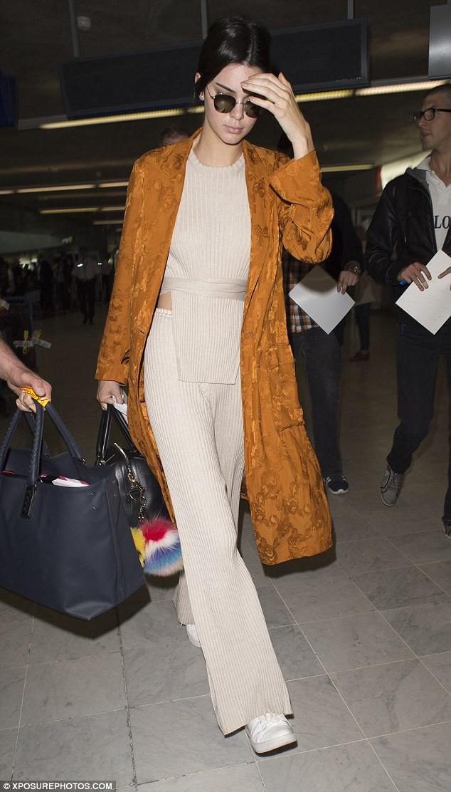 Kendall Jenner, always the sneaker style star, looked stylish in a kimono-style coat, a knitted tabard top and loose-fitting trousers by Elle Sasson, and a pair of her favorite Kenneth Cole 'Kam' Sneakers.