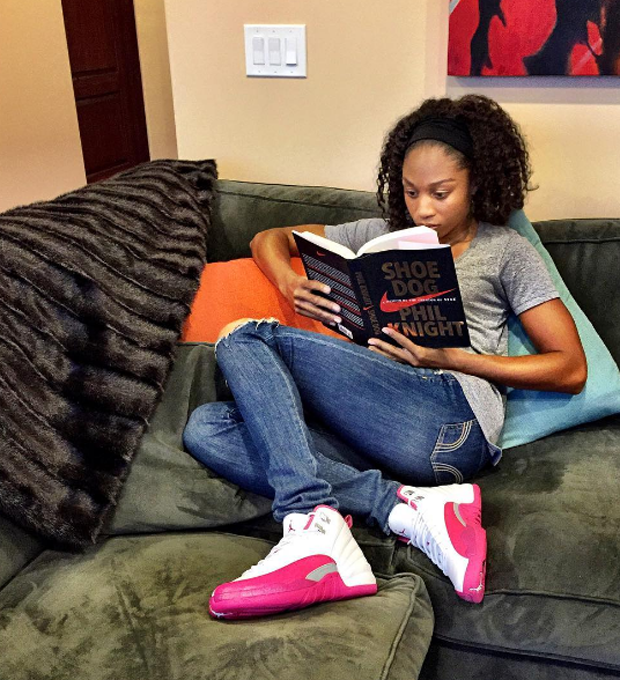 "Allyson Felix sat down with a good read ( 'Shoe Dog' by Phil Knight ) in the  Air Jordan 12 ""Vivid Pink."""