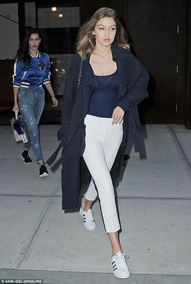 Gigi Hadid made her way through NYC with sister Bella in tow.  The model stepped out gorgeous in white trousers and a pair of adidas Superstar Sneakers.